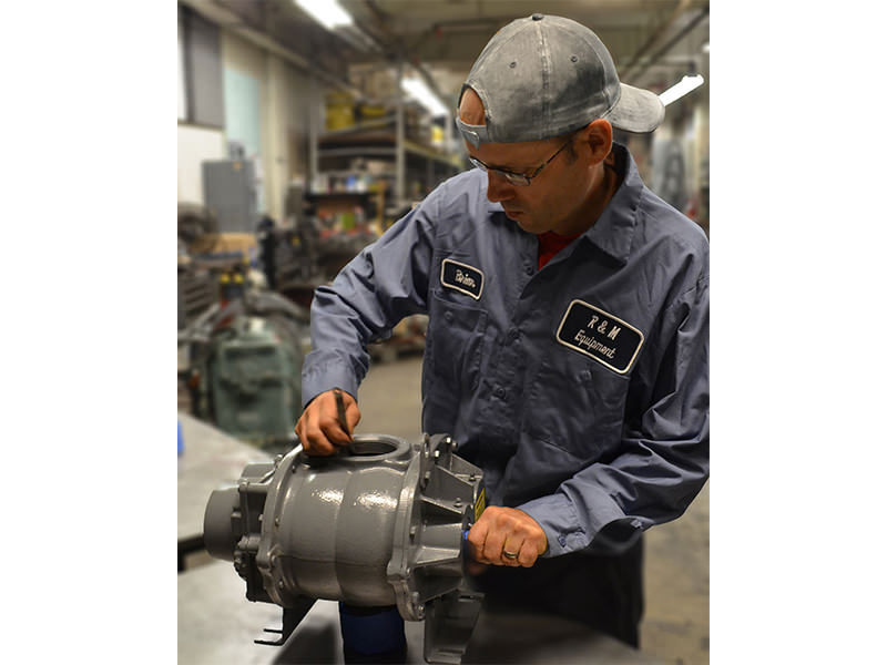 A service technician checks tolerances on a blower repair.